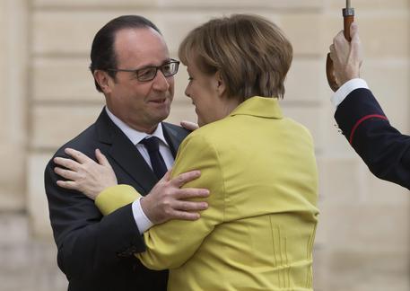 Un abbraccio fra Angela Merkel e Francois Hollande (foto: Ansa)